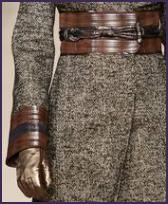 The tweed coat shown here is by Pollinini and leather has been used to create a faced outer top cuff and matching wide belt.