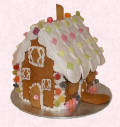 The Gingerbread House Recipe after it has been assembled and decorated with fondant and sweets.