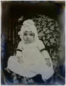 C19th tintype image of baby in mourning and wearing black armband ribbons.