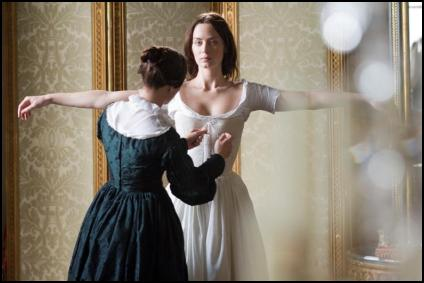 Film still of the young Victoria being helped into her corsetry undergarments.