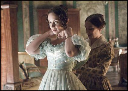 Film still of the young Victoria being assisted with dressing.
